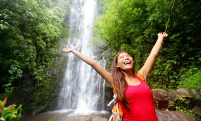happy-traveller-in-front-of-waterfall